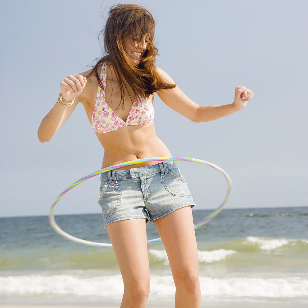 Young woman playing with hula hoop