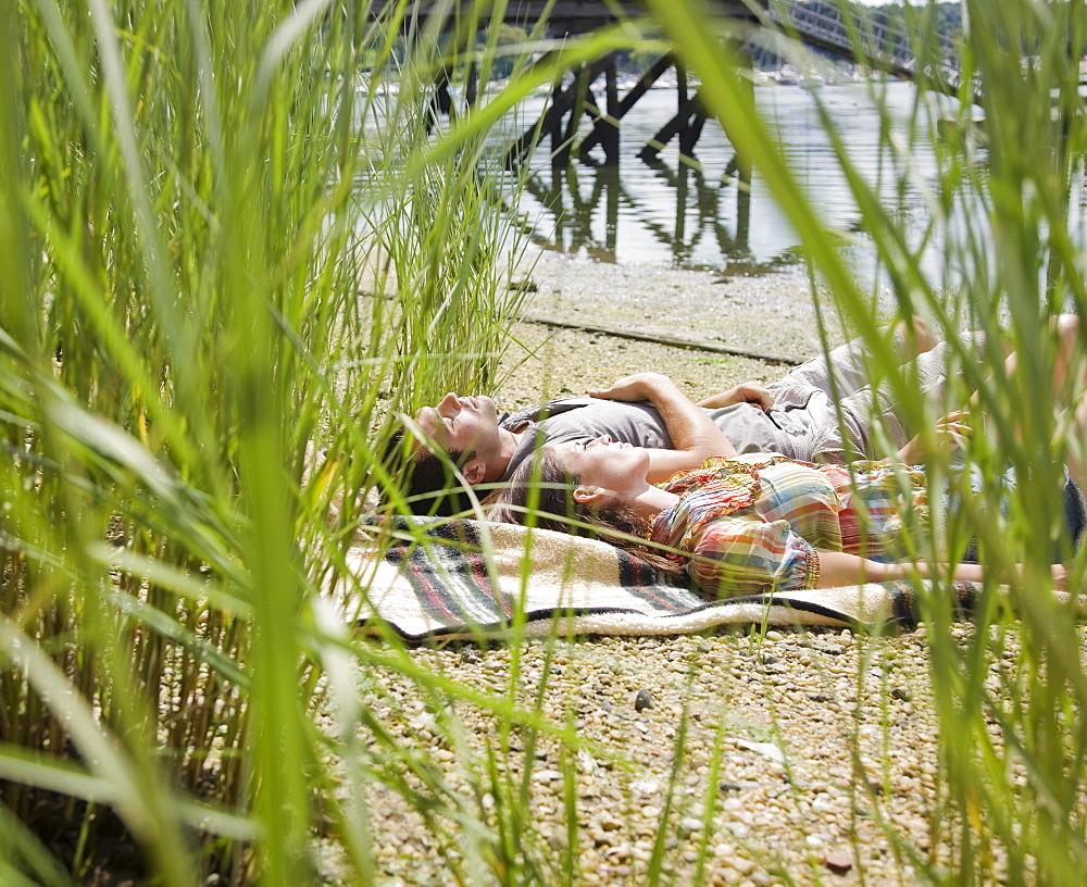 Couple laying on blanket near lake