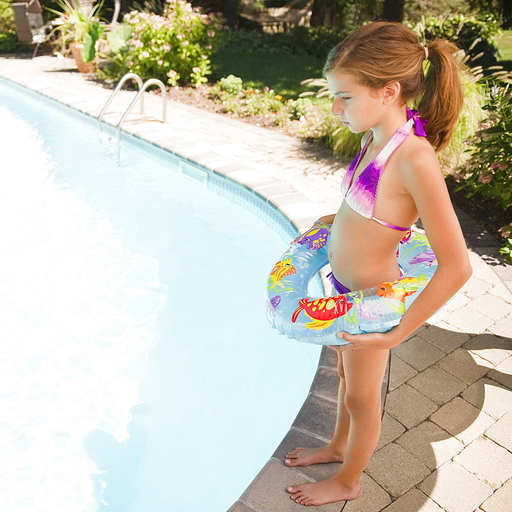 USA, New York, Girl (10-11) standing next to swimming pool