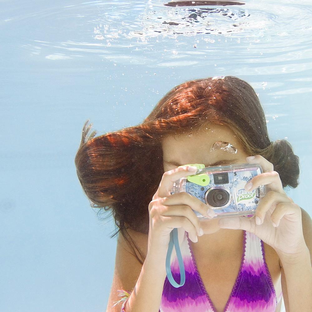 USA, New York, Girl (10-11) taking photo in swimming pool