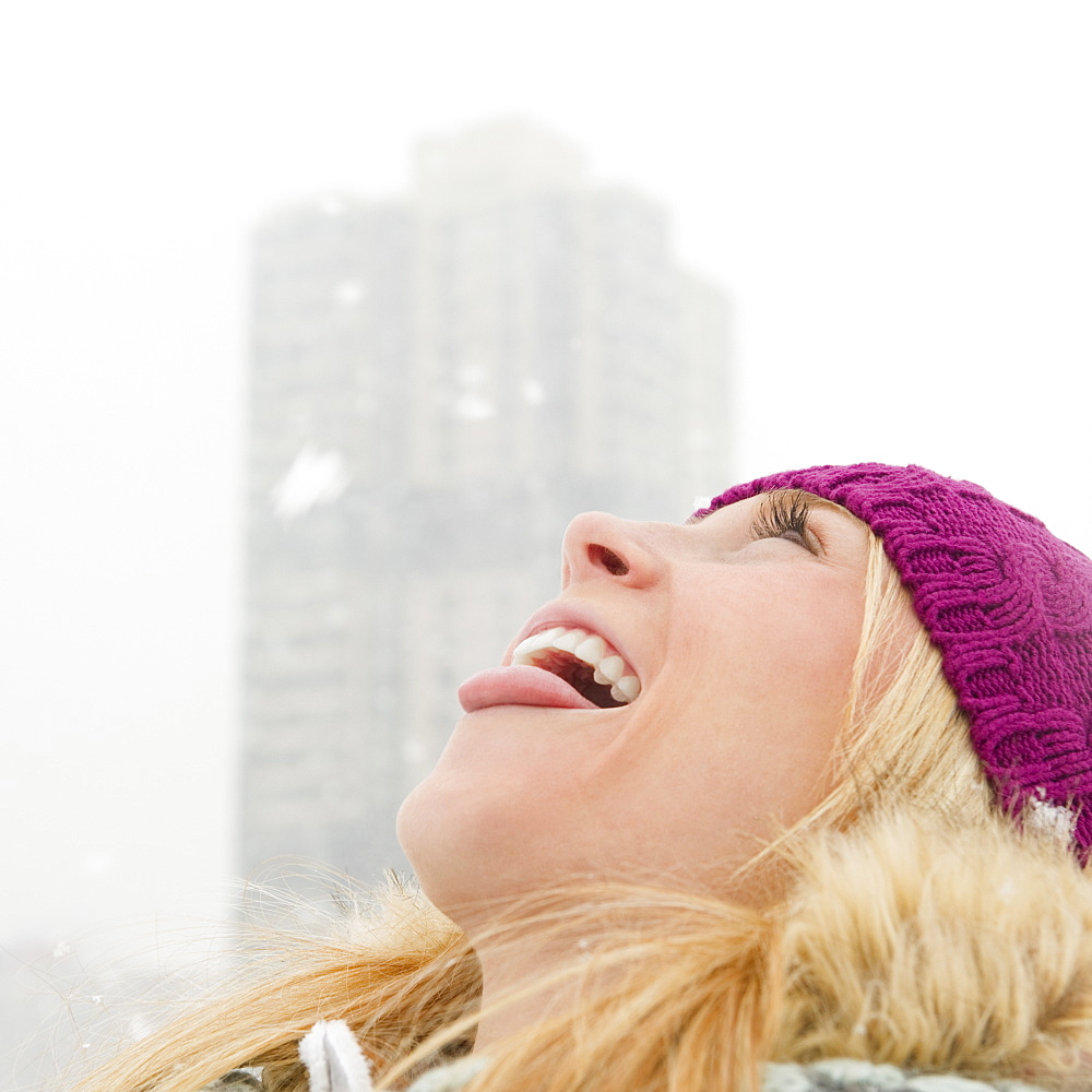 USA, New Jersey, Jersey City, woman catching snowflakes with tongue
