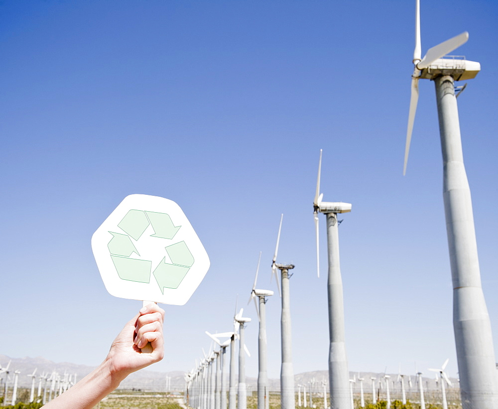 USA, California, Palm Springs, Coachella Valley, San Gorgonio Pass, Woman's hand holding recycling sign against blue sky and wind turbines