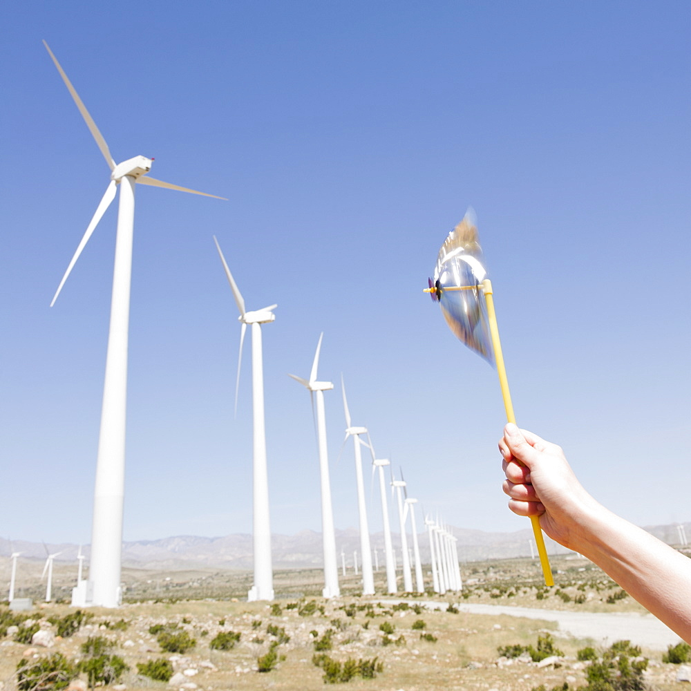 USA, California, Palm Springs, Coachella Valley, San Gorgonio Pass, Woman's hand holding pinwheel against blue sky and wind turbines