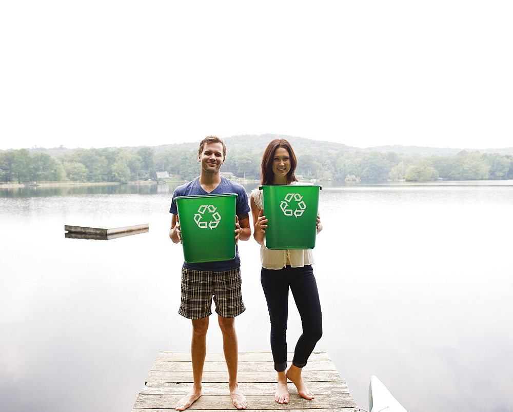 USA, New York, Putnam Valley, Roaring Brook Lake, Couple standing on pier with recycling bins