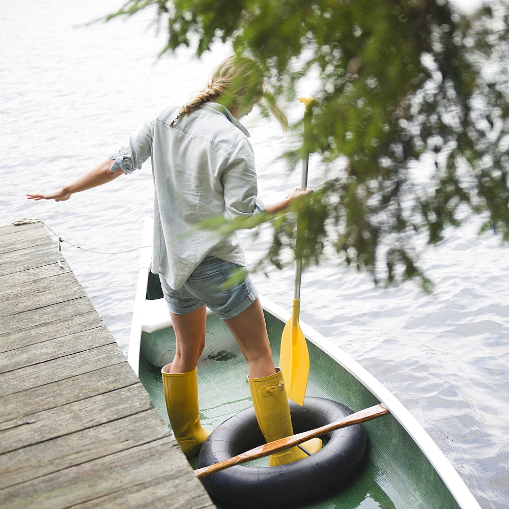 Roaring Brook Lake, Woman standing in boat with paddle