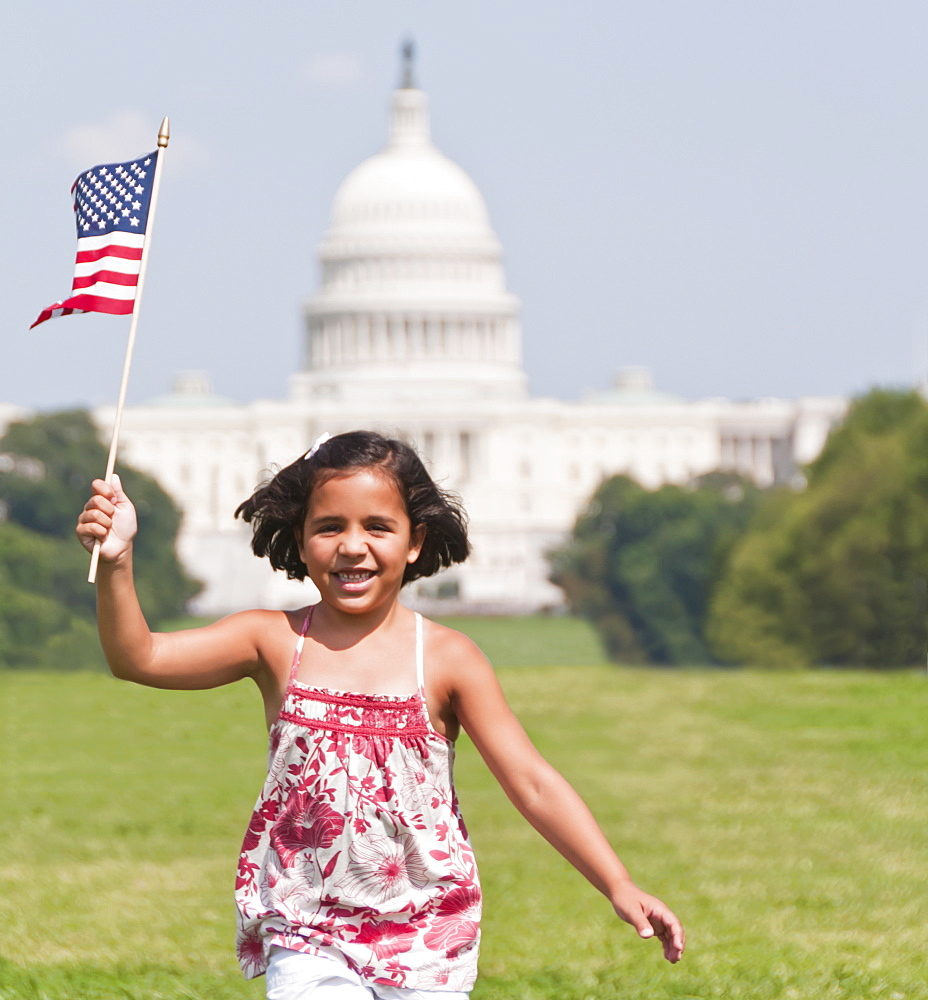 USA, Washington DC, girl (10-11) with US flag running in front of Capitol Building