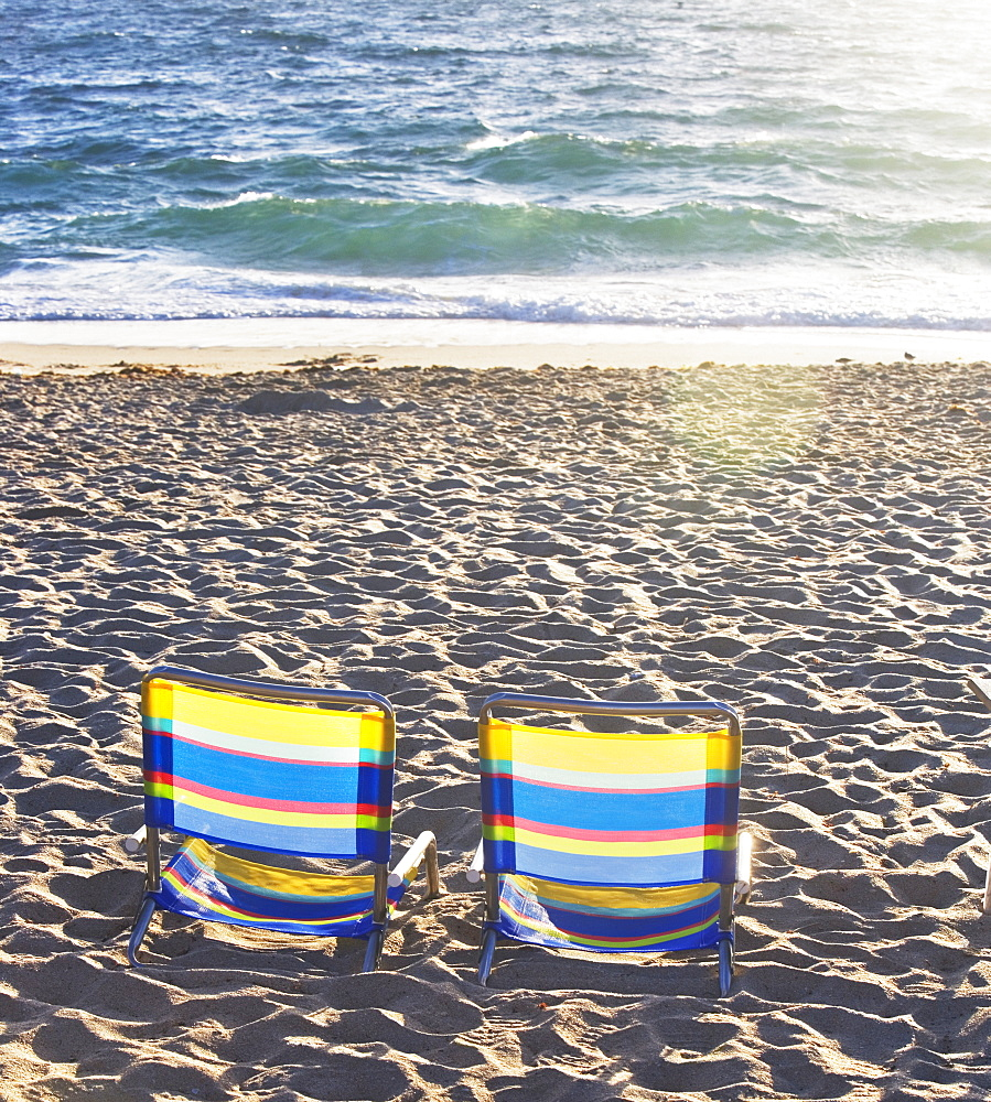 Empty beach chairs on sand