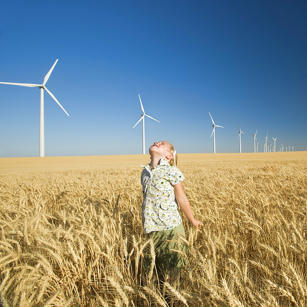 Girl looking to sky on wind farm