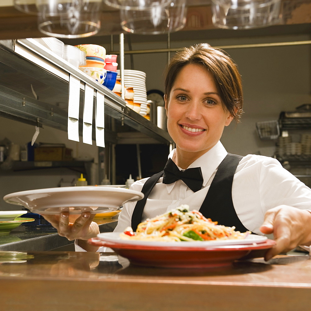 Waitress taking plates of food from kitchen