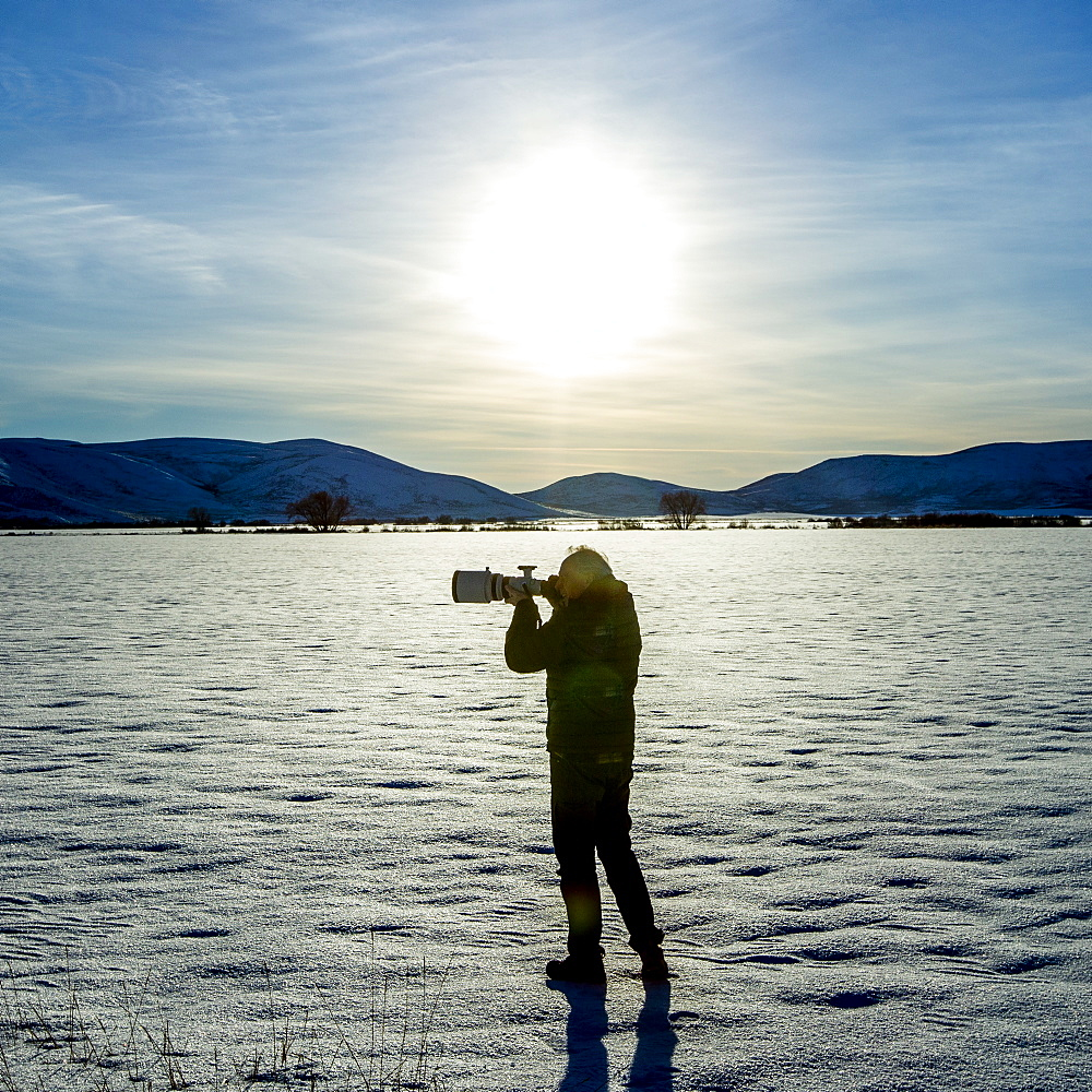 Senior man photographing in snow field in Picabo, Idaho