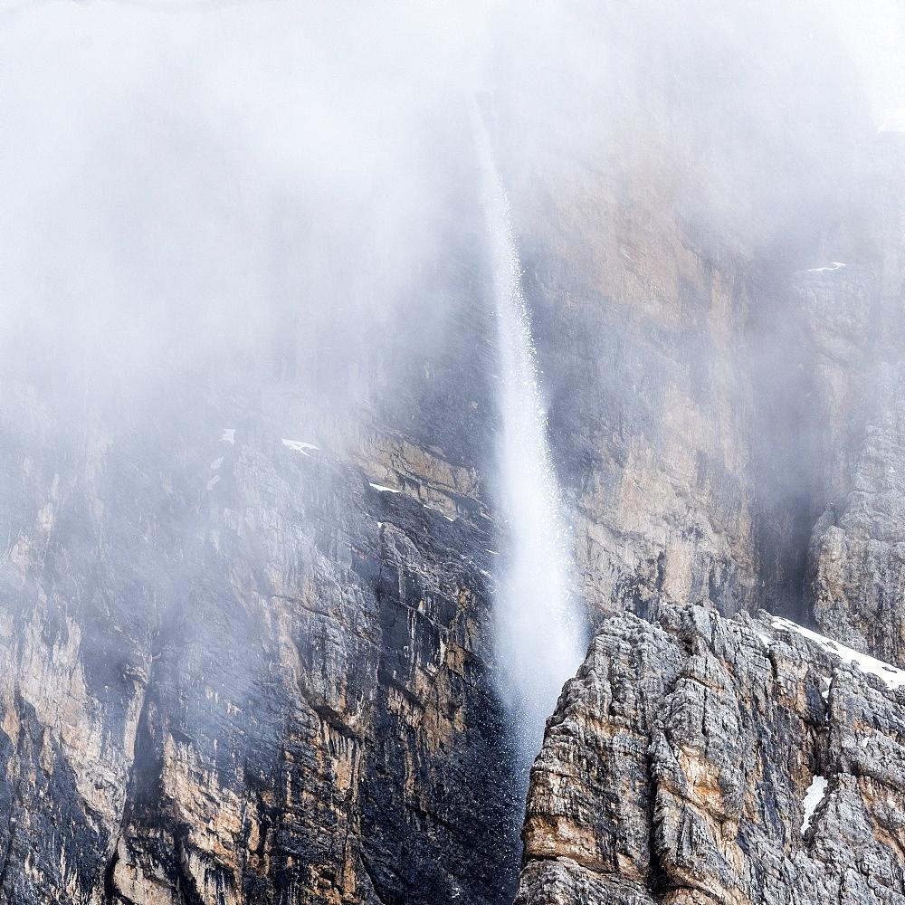 Snow falling down cliff in Dolomites, Passo Giau, Belluno, Italy