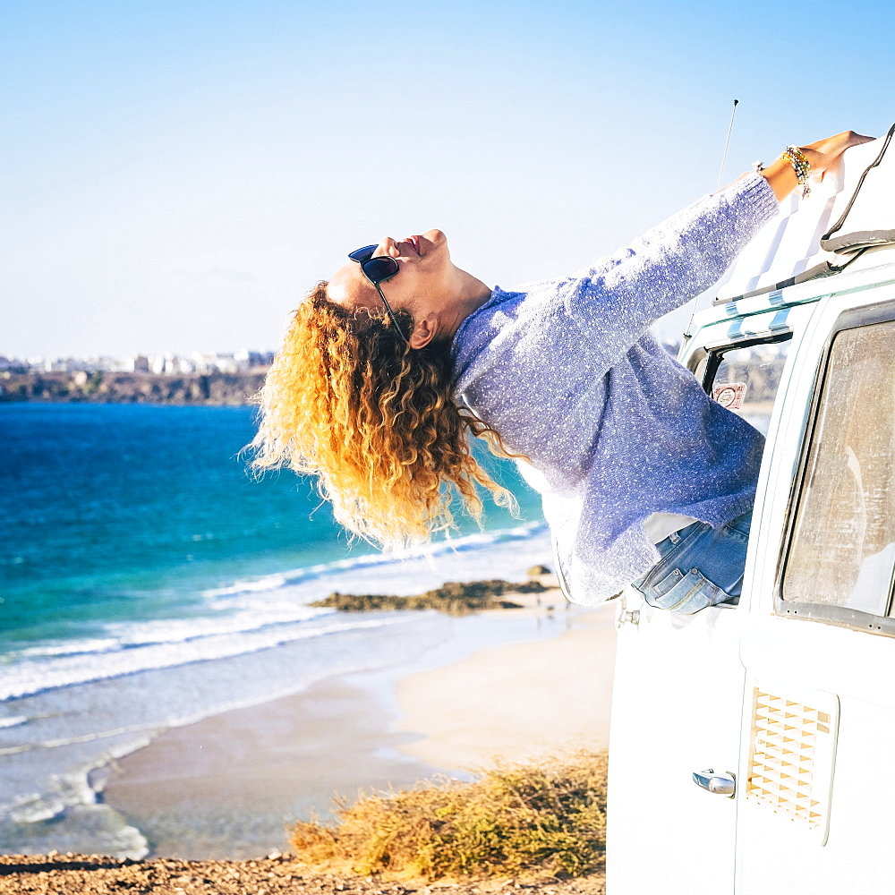 Woman leaning out of camper van window by beach in Fuerteventura, Canary Islands