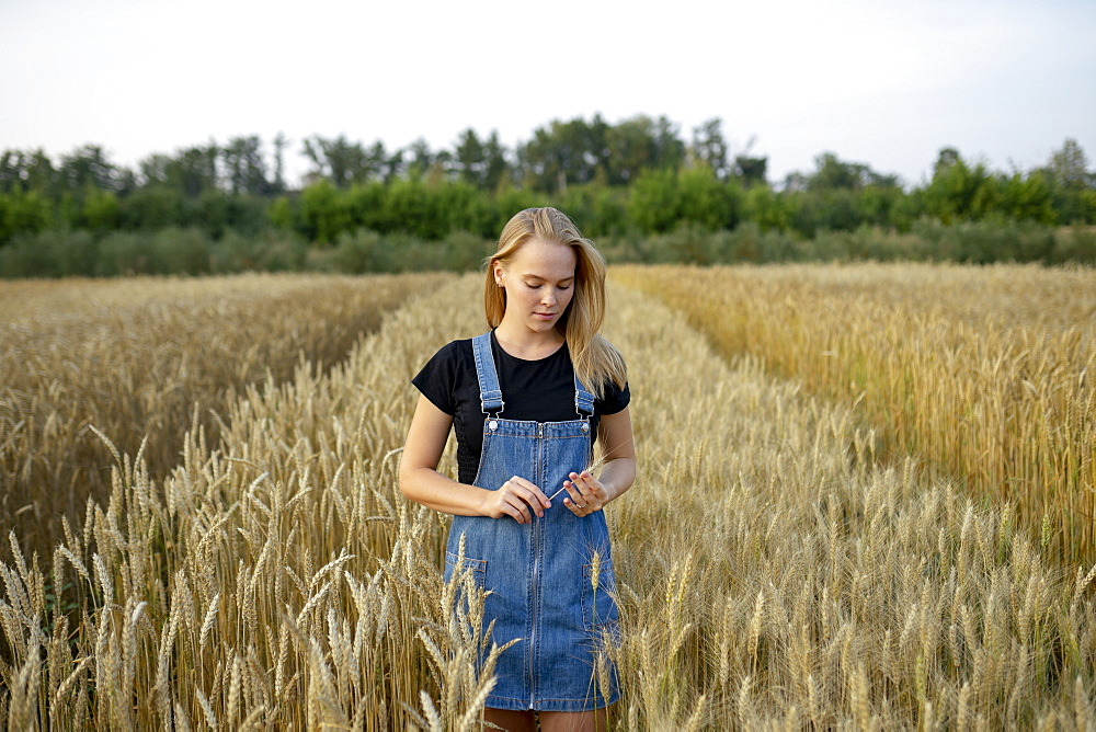Young woman wearing overall dress in wheat field