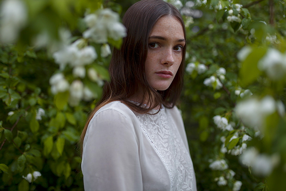 Young woman among white blossoms
