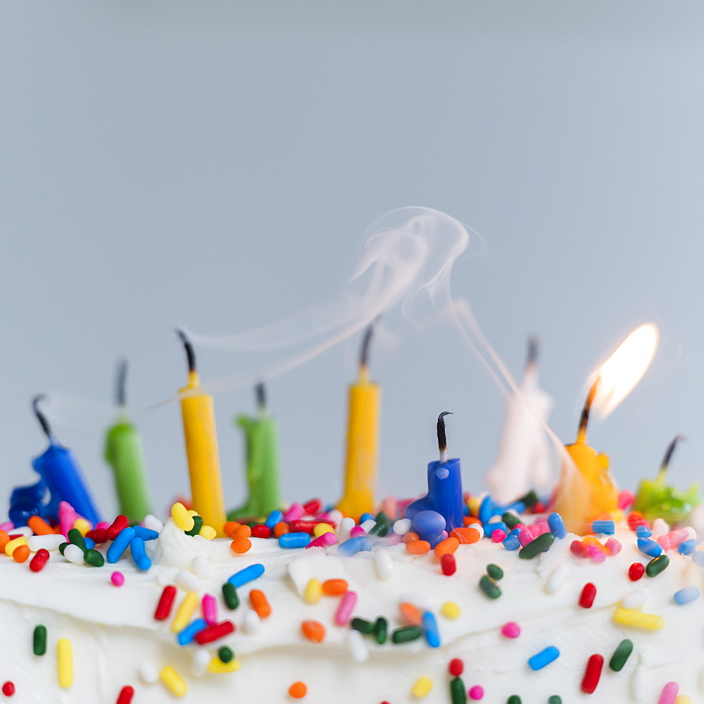 Extinguished birthday candles on cake - one still burning