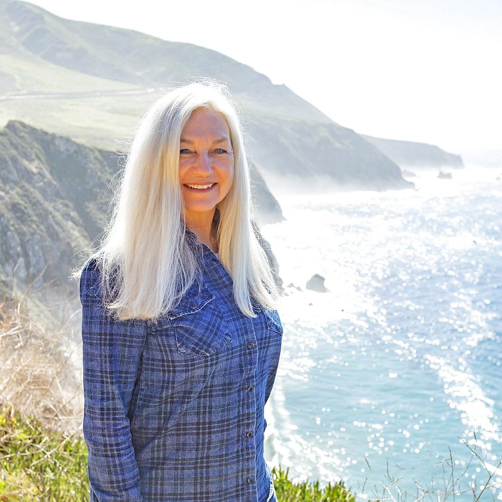USA, California, Big Sur, Portrait of senior woman against cliffs and sea