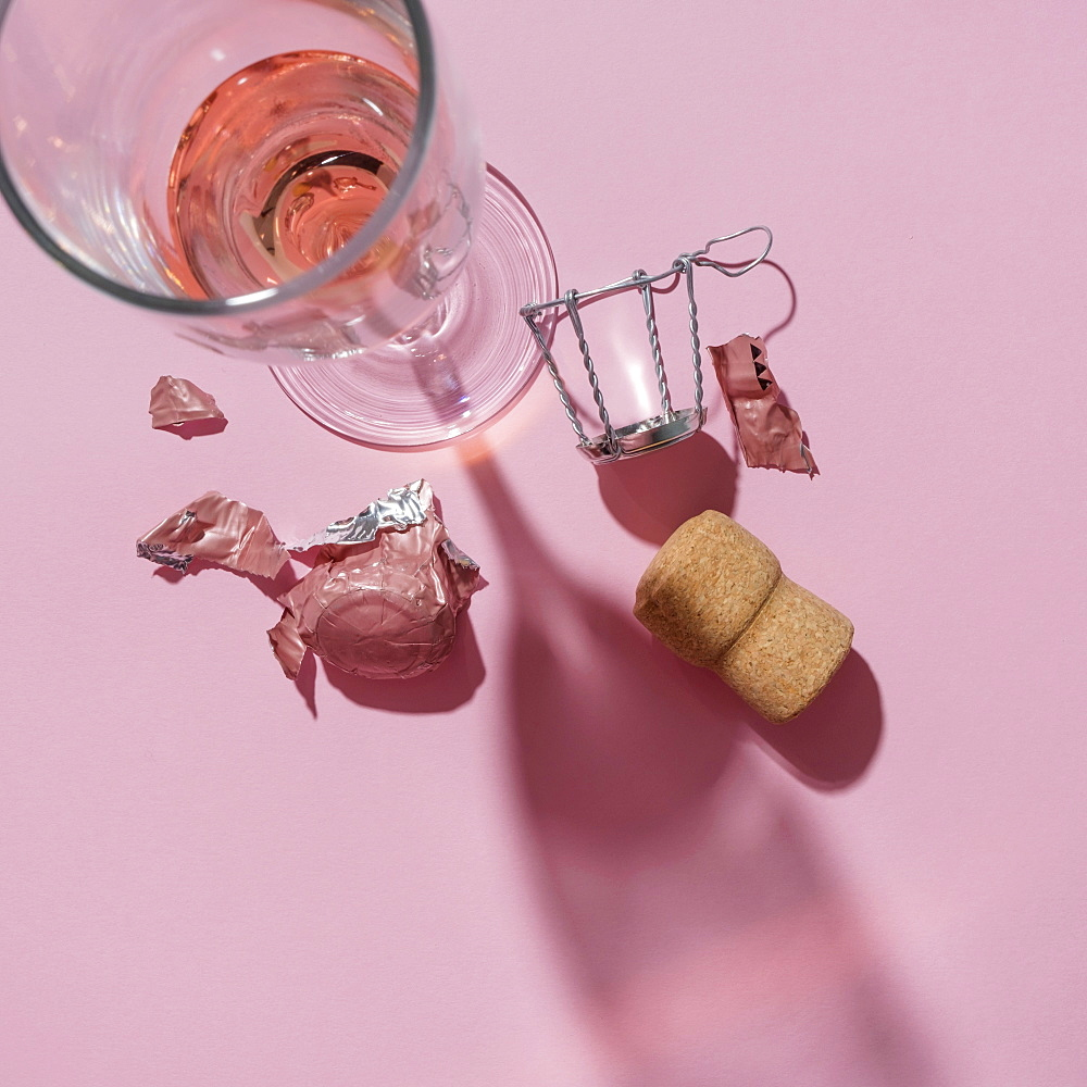 Studio shot of Champagne cork and wineglass on pink background