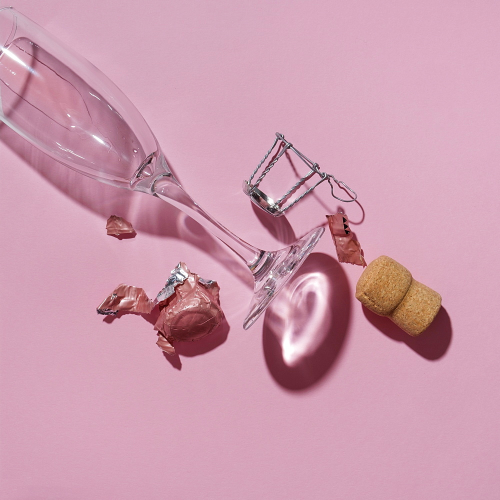 Studio shot of Champagne cork and empty wineglass on pink background
