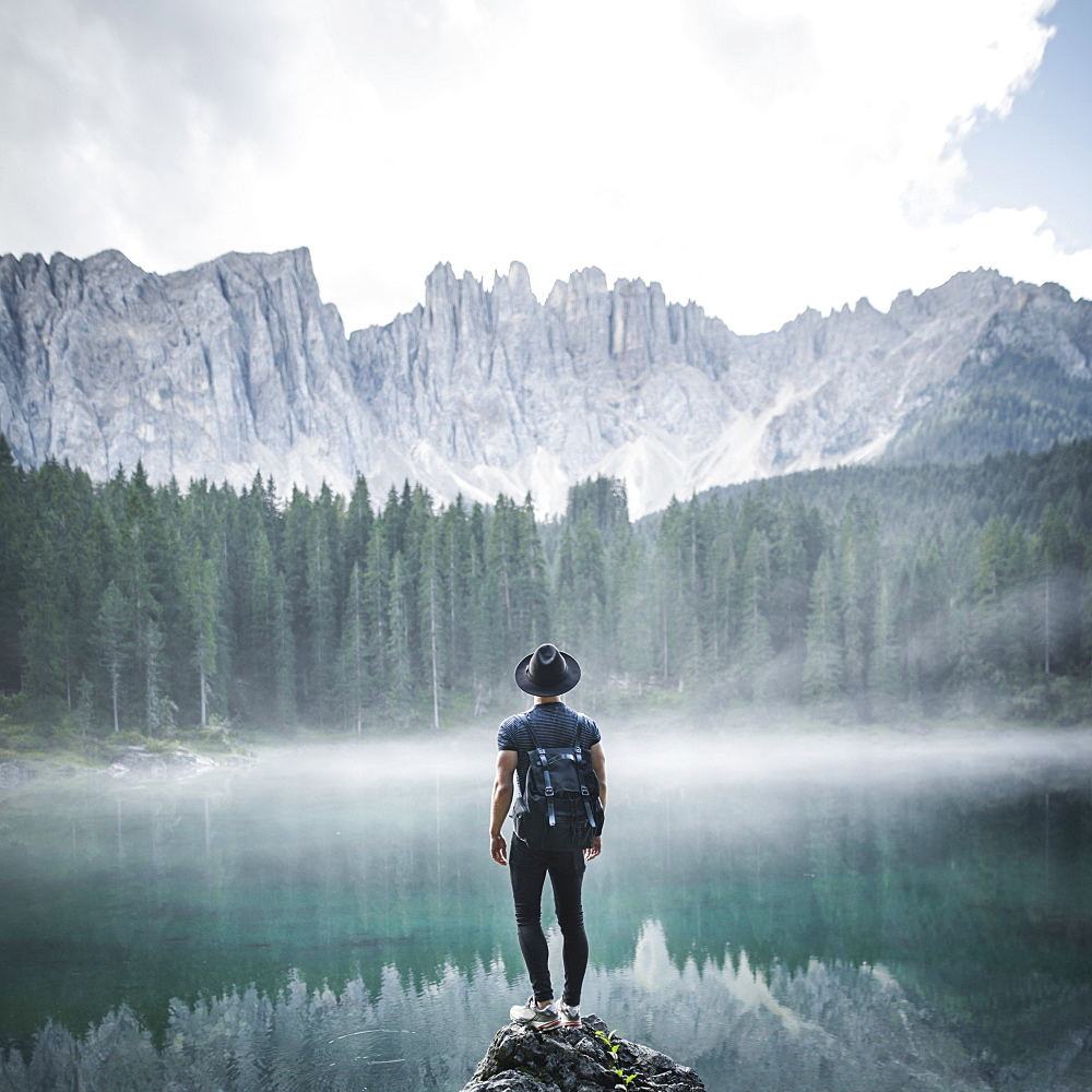 Italy, Carezza, Young man standing on rock at Lago di Carezza in Dolomite Alps at dawn