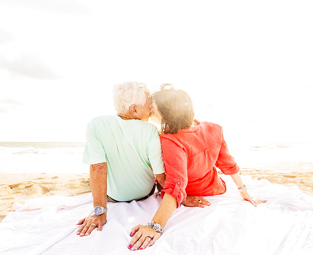 Rear view of couple kissing on beach at sunrise, Jupiter, Florida