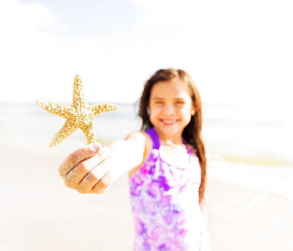 Portrait of girl (6-7) holding starfish on beach, Jupiter, Florida