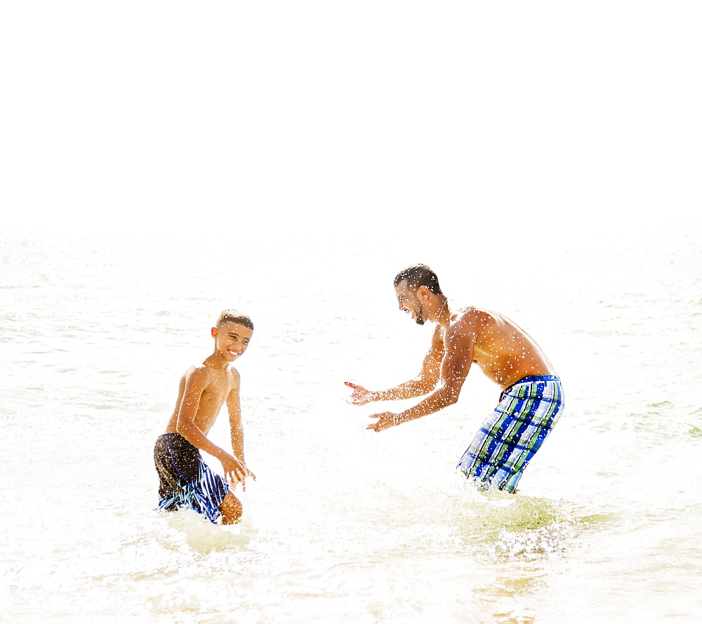 Father and son (10-11) having fun on beach