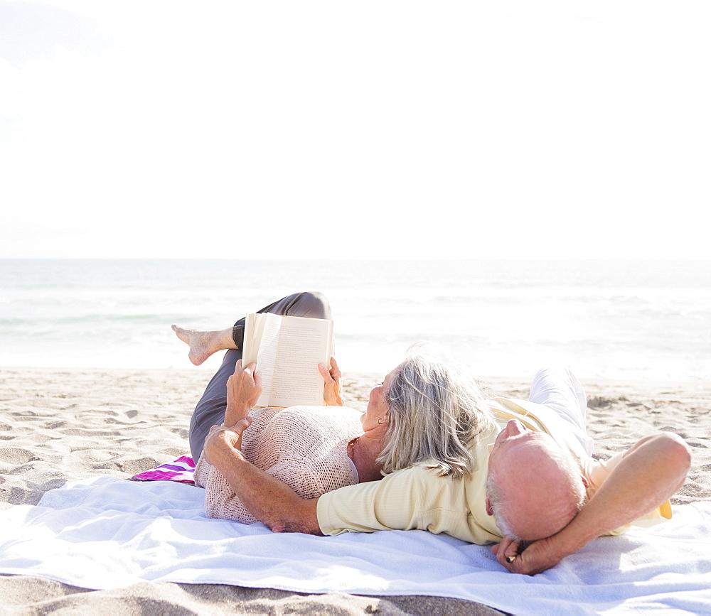 Senior couple reading books on beach
