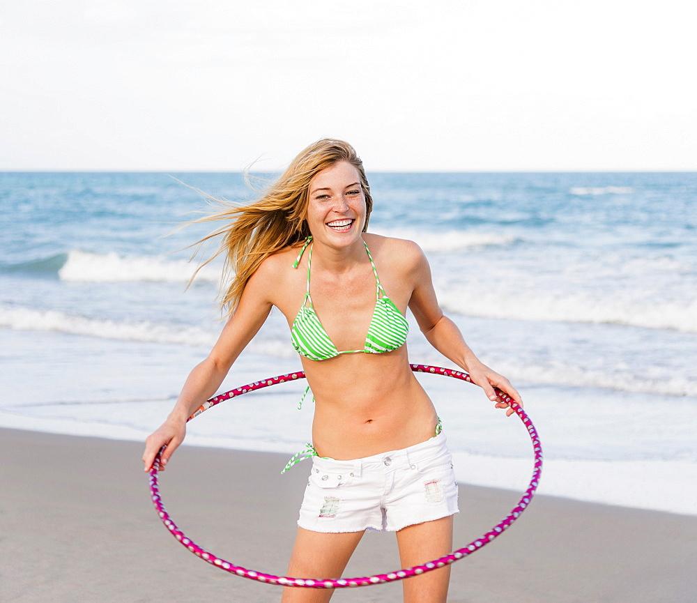 Young woman on beach twirling Hula hoop, Jupiter, Florida, USA