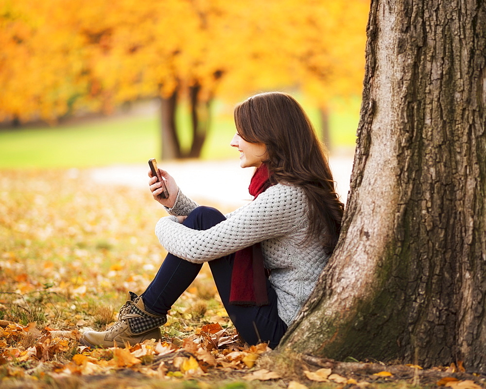 Young woman using cell phone in Central Park, USA, New York State, New York City
