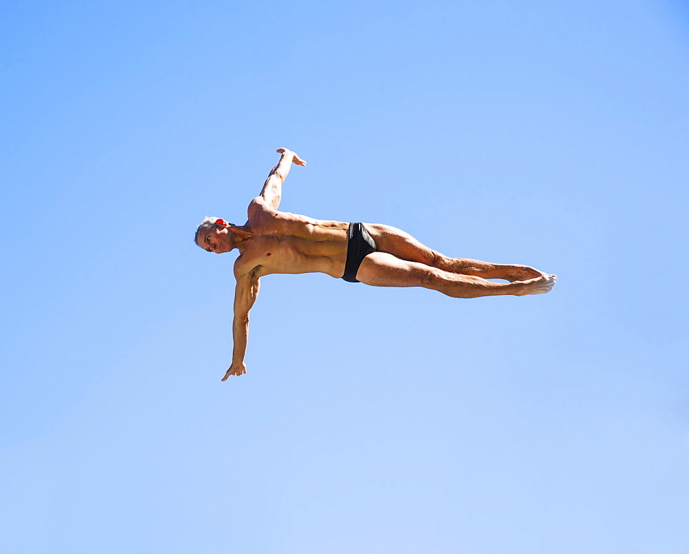 Athletic swimmer mid-air against blue sky