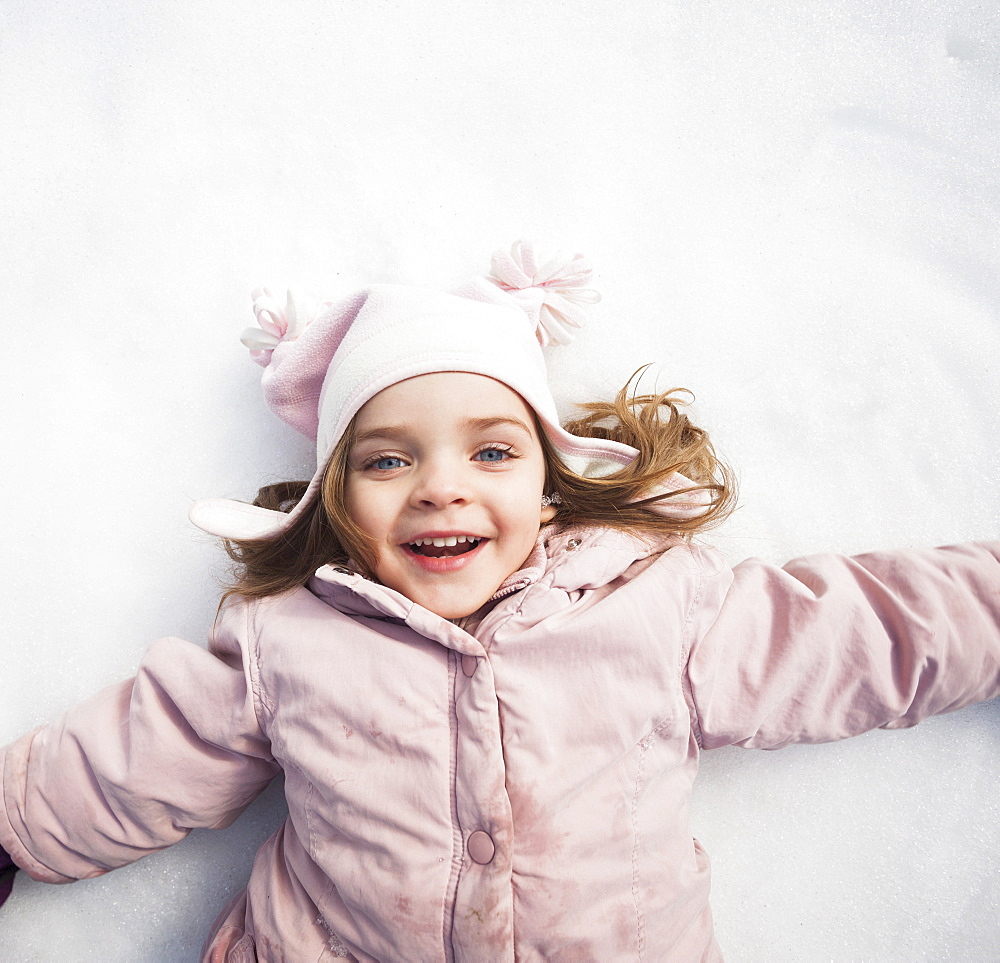 Directly above portrait of girl (2-3) lying on snow