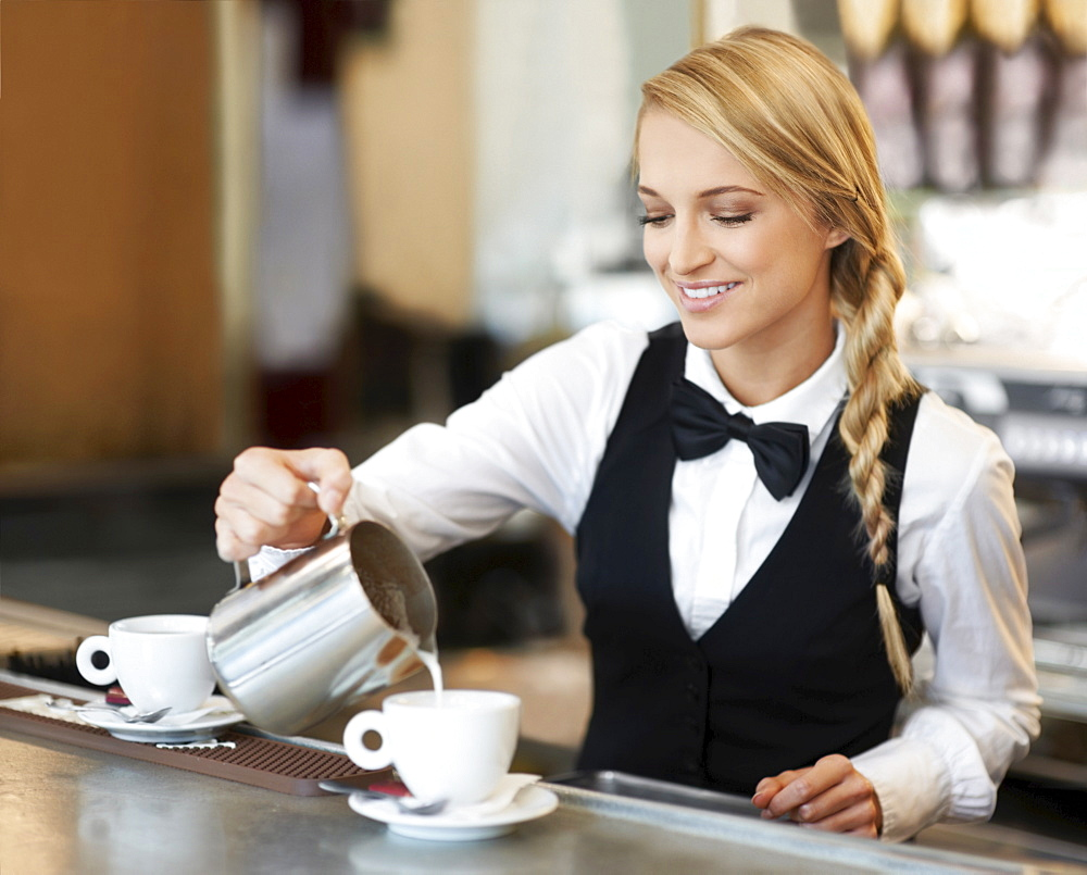 Female barista pouring milk into coffee cup