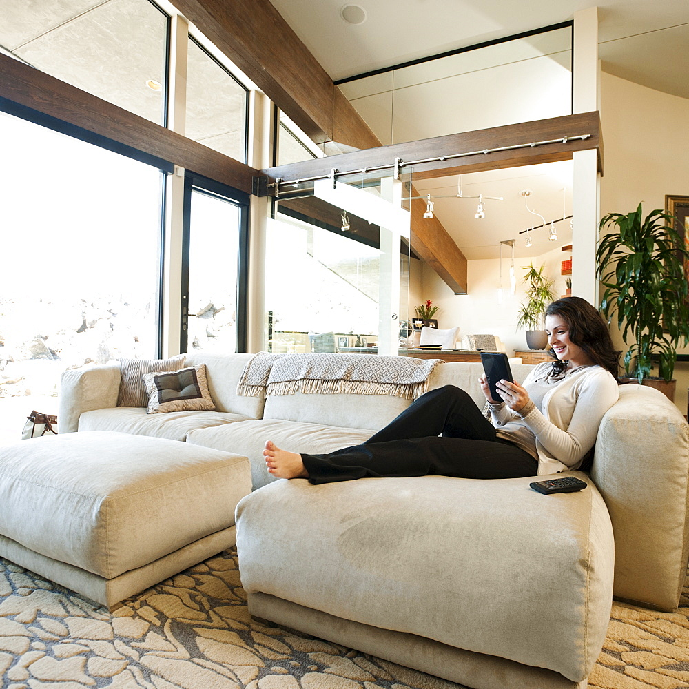 Woman using tablet while sitting on couch, USA, Utah, St George
