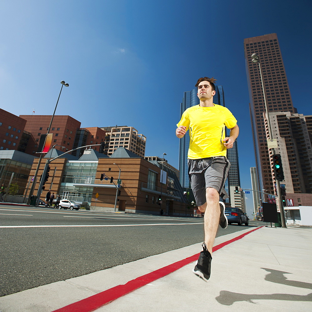 USA, California, Los Angeles, Young man running on city street, USA, California, Los Angeles