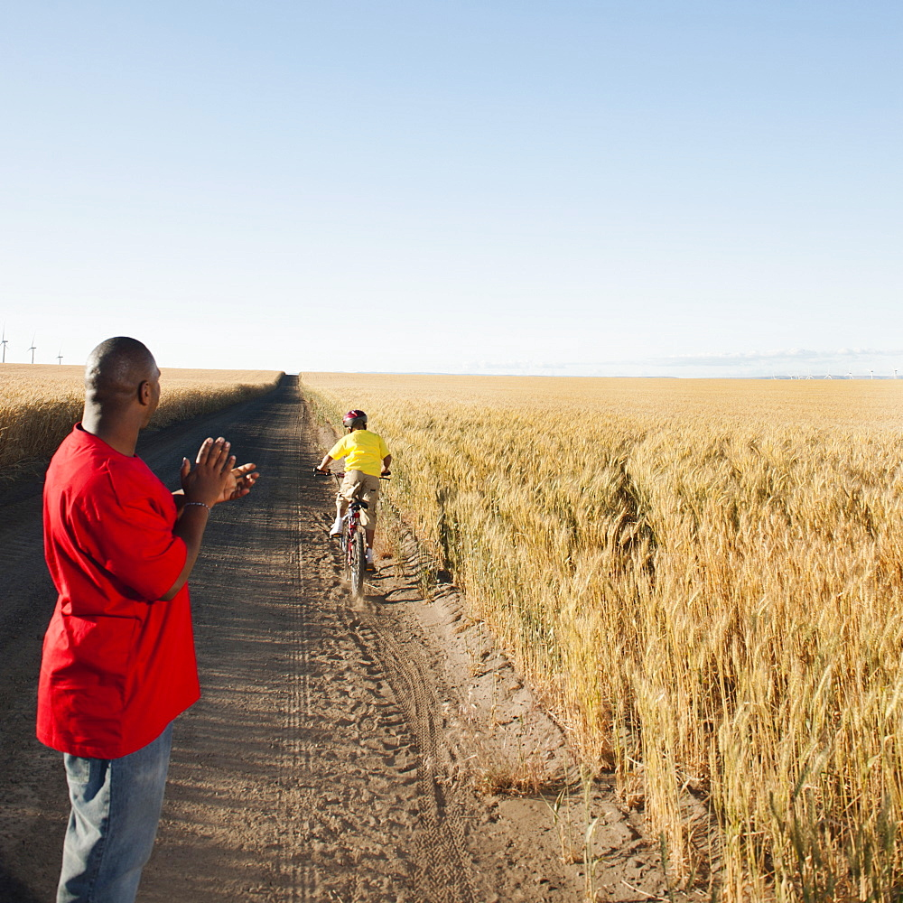Father clapping as son (8-9) is cycling along dirt road in fields
