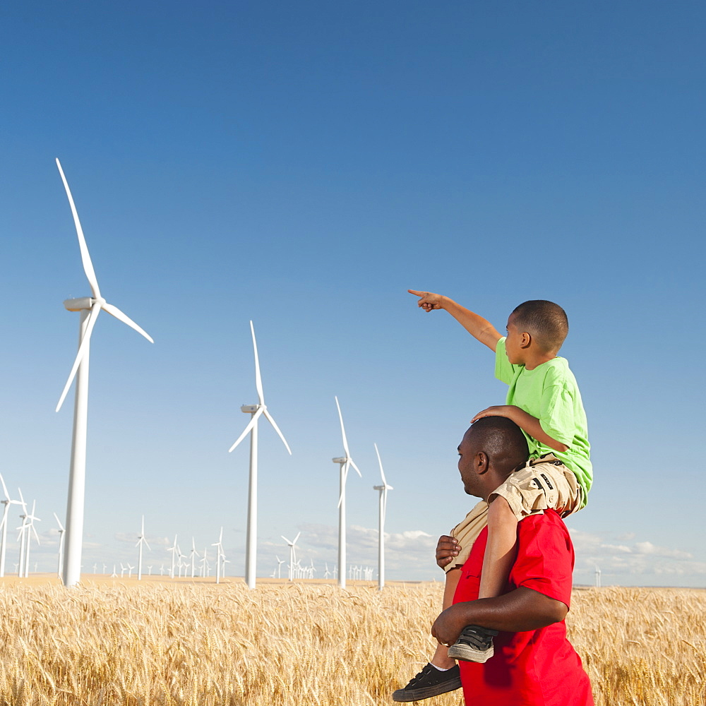 USA, Oregon, Wasco, Boy (8-9) piggy-back riding on father pointing at wind turbines