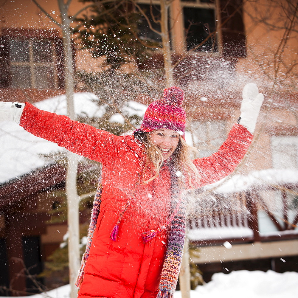 USA, Utah, Salt Lake City, Portrait of young woman playing in snow