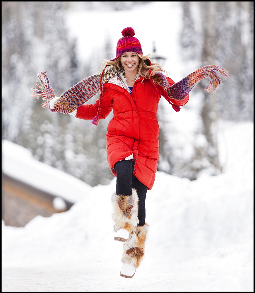 USA, Utah, Salt Lake City, Portrait of young woman skipping in snow