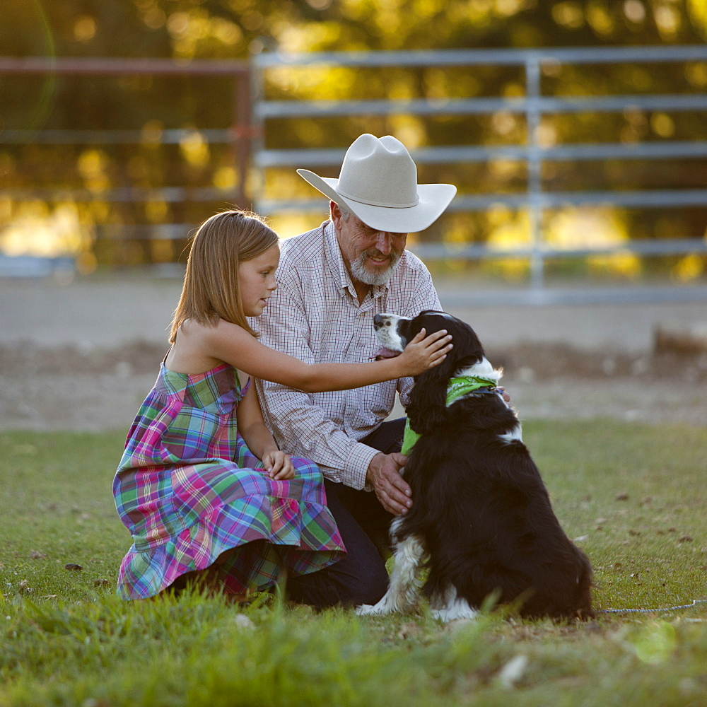 Girl (8-9) stroking dog with grandfather