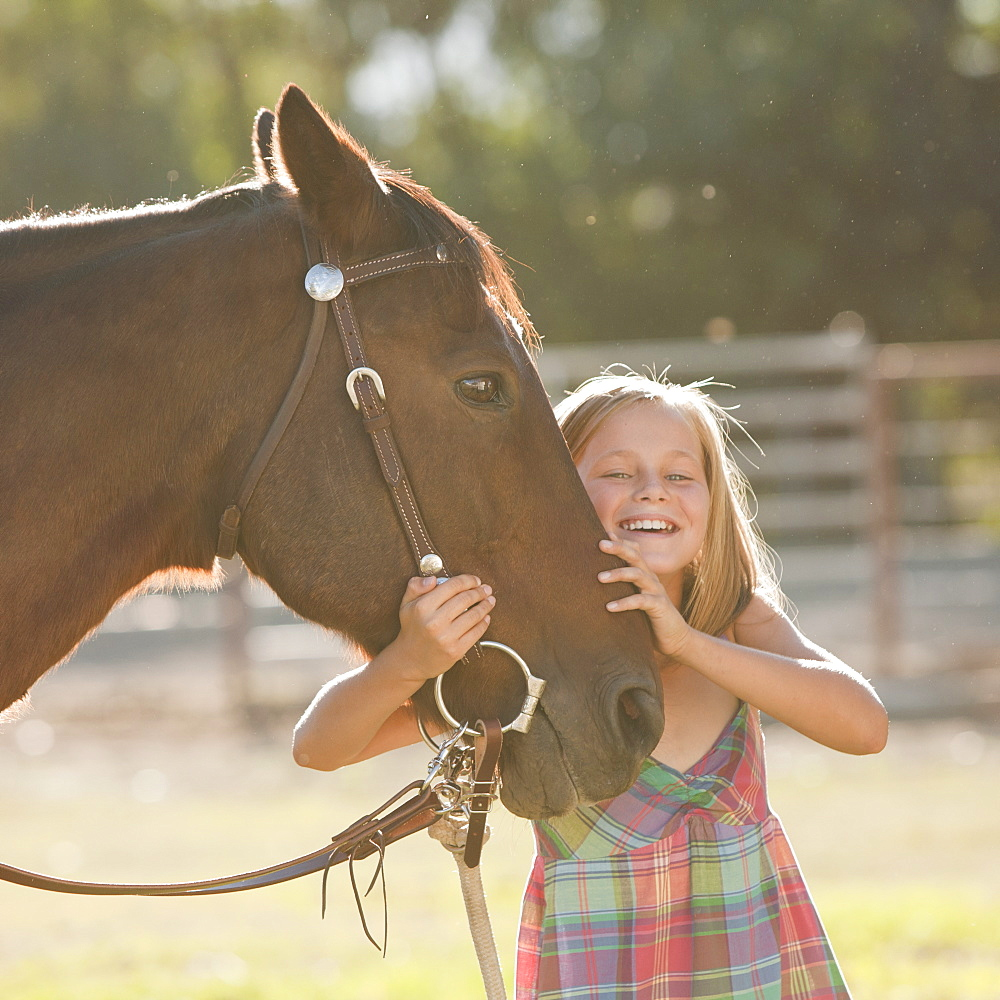 Portrait of smiling cowgirl (8-9) with horse in ranch