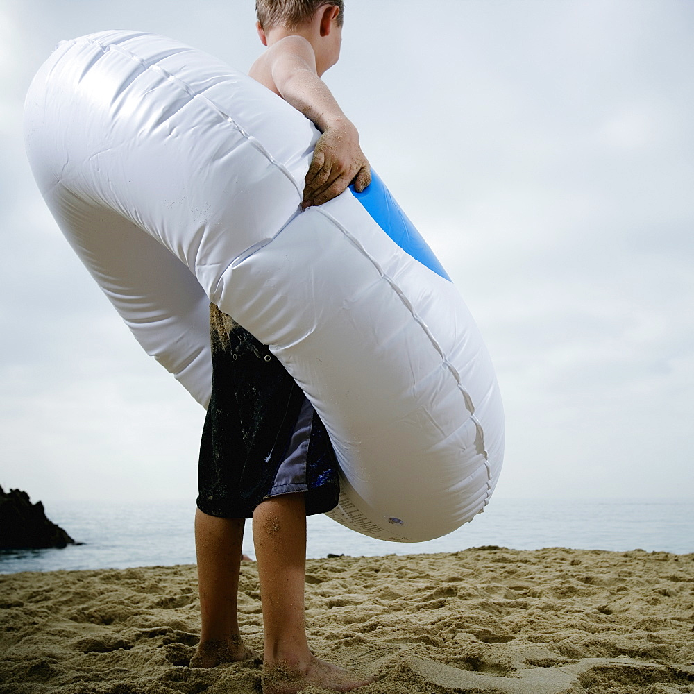 Young boy standing in an inflatable tube at the beach
