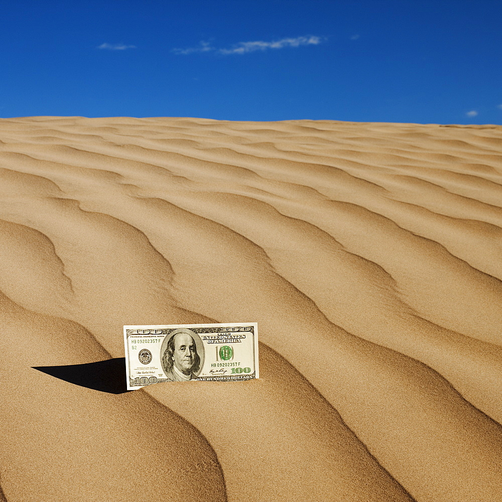 100 dollar bill on sand in desert