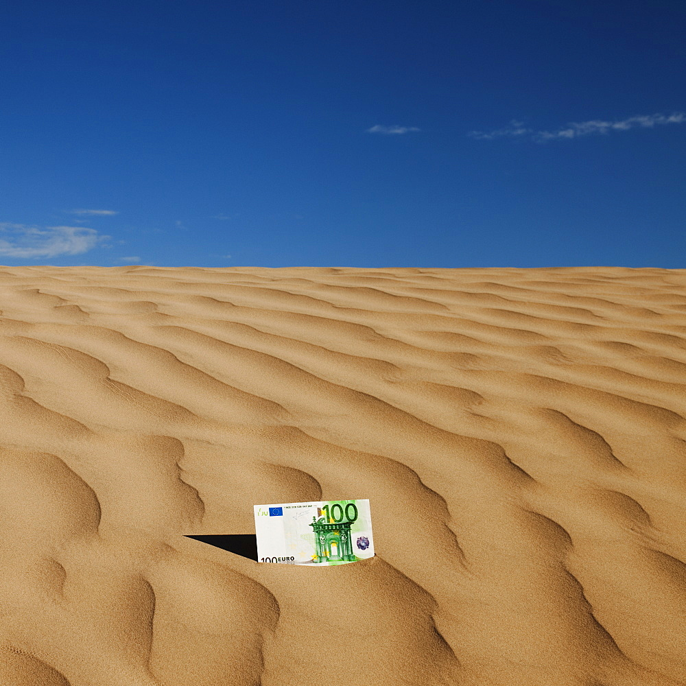 100 euro bill on sand in desert