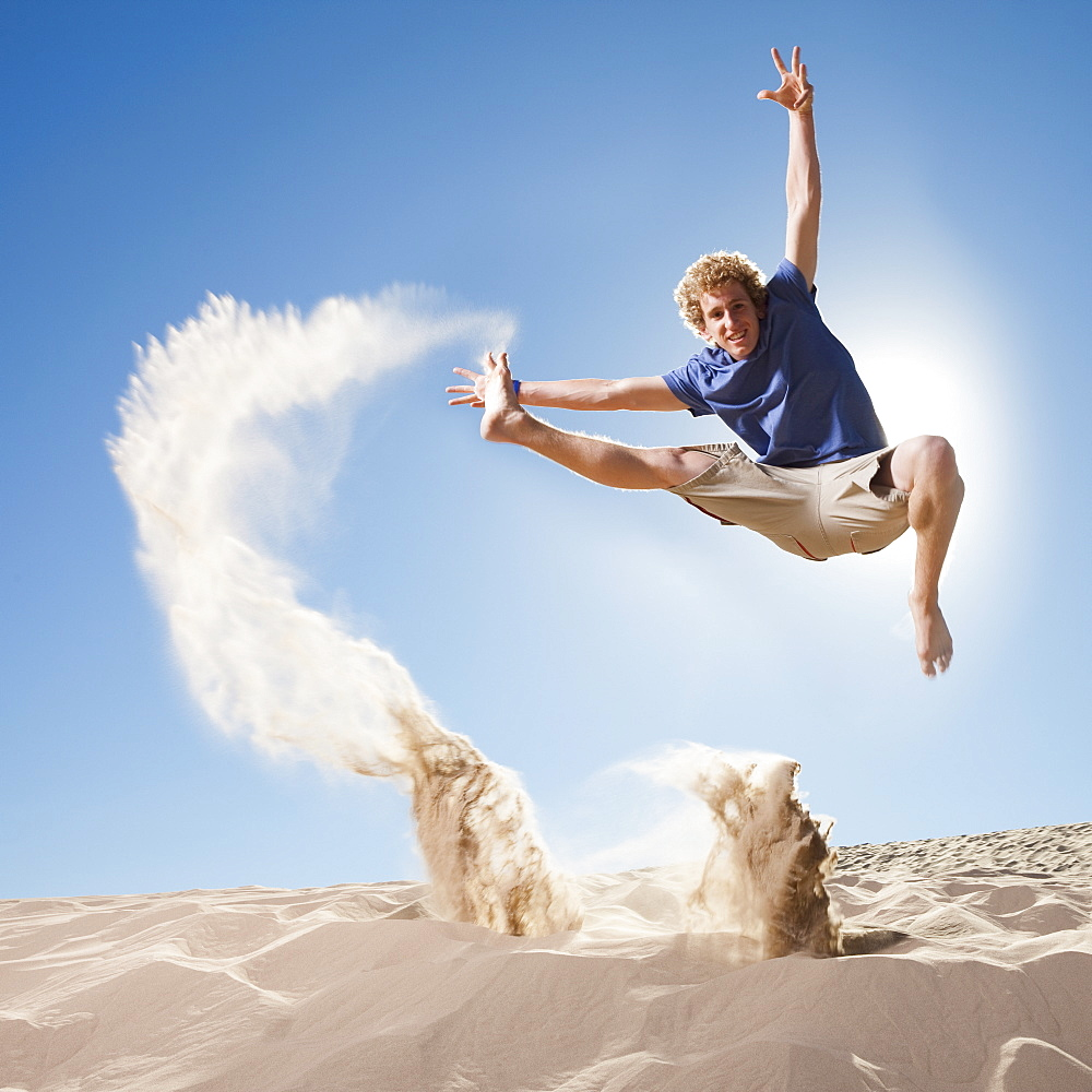 Energetic man jumping in the sand