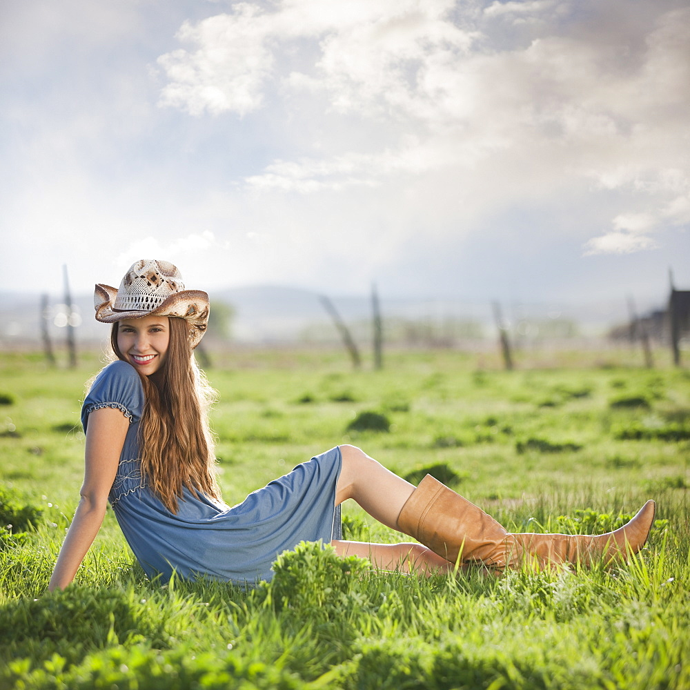 Cowgirl relaxing in field