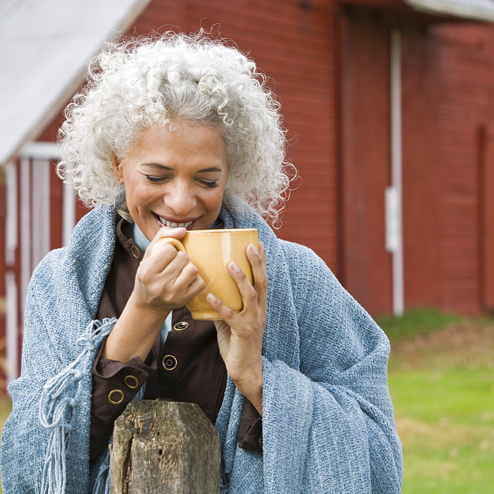 Woman holding mug outside