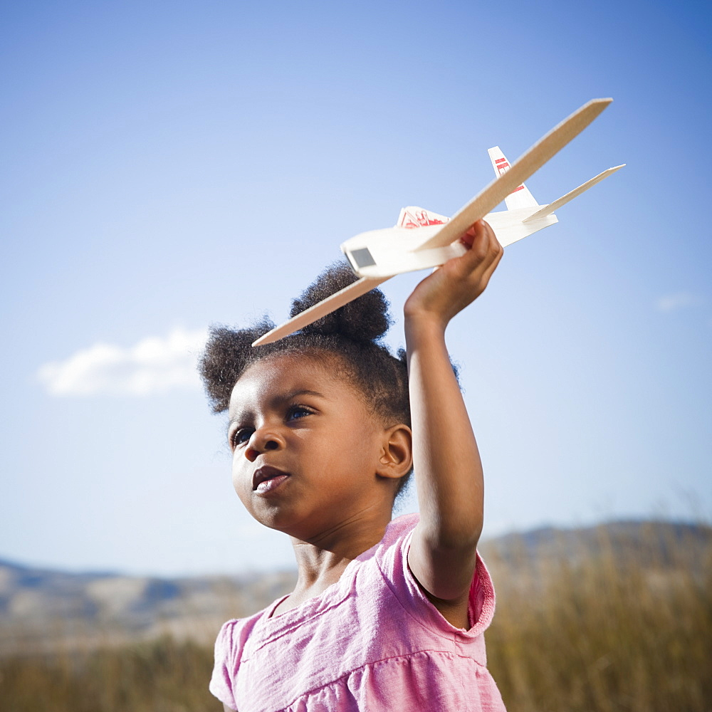 Young girl playing with toy airplane