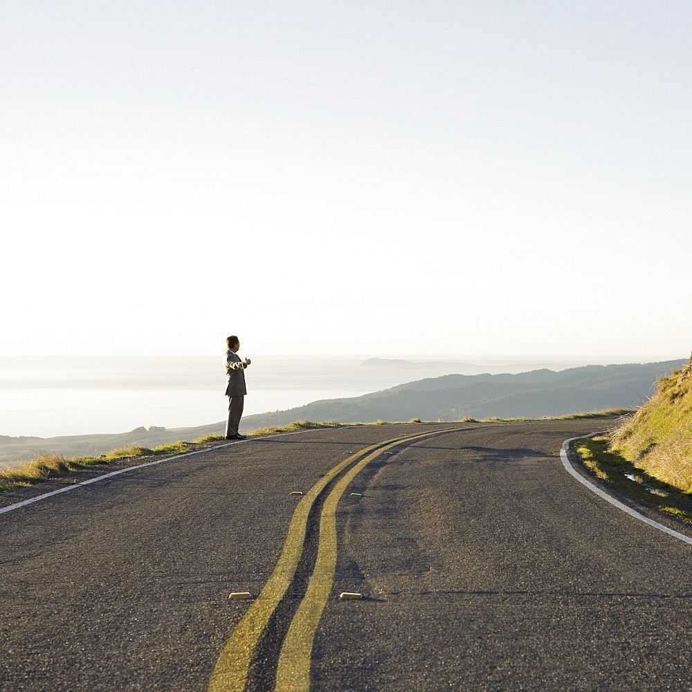 Businessman standing on remote road