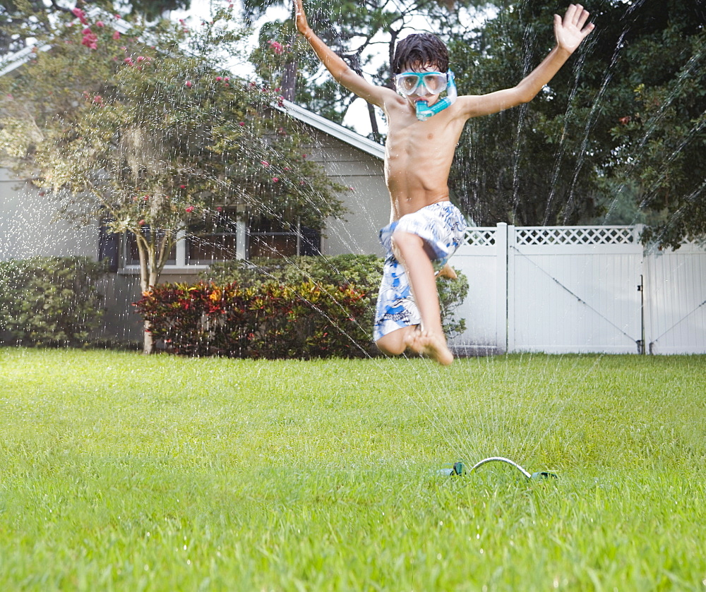 Boy jumping through sprinkler