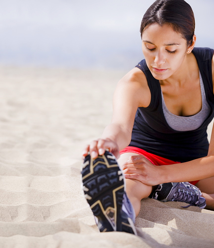 Runner stretching on beach